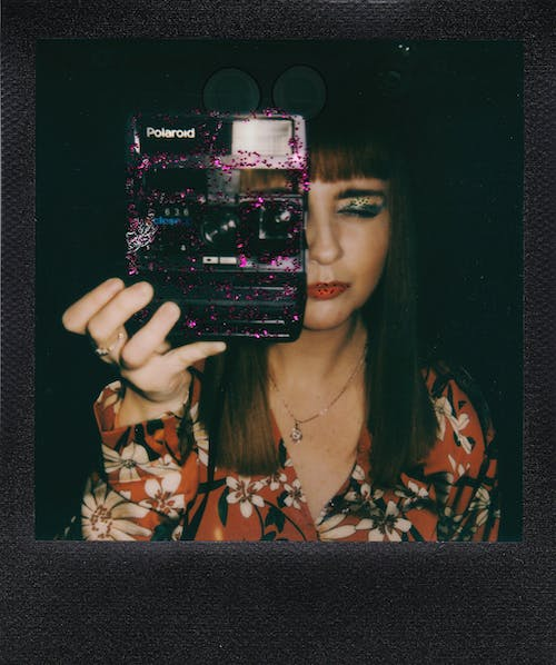 Woman in Black and Pink Floral Shirt Holding Black Smartphone