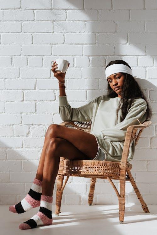 Gratis arkivbilde med afrikansk-amerikansk kvinne, beina krysset, drikke