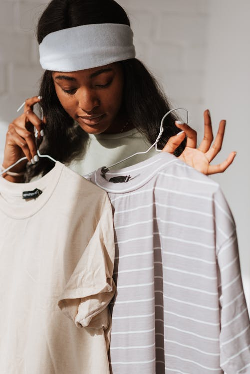 Black woman choosing wear while showing good gesture in sunshine