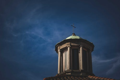 Old orthodox church with cross on roof under blue sky