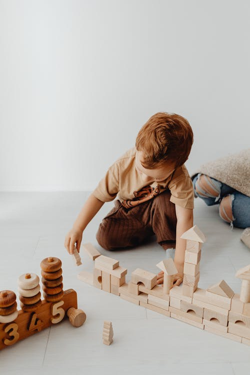 Photo of a Child Stacking Wooden Building Blocks