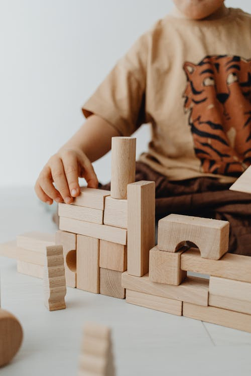Selective Focus Photo of a Kid Stacking Building Blocks