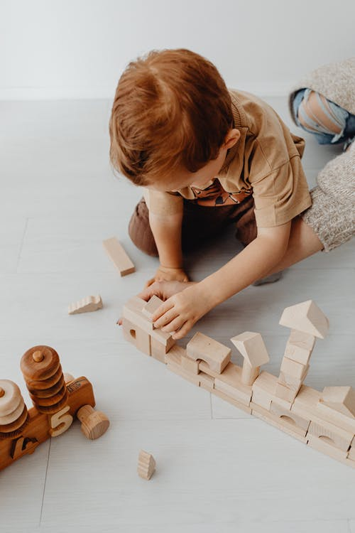 Kid in a Brown Shirt Playing with Wooden Building Blocks