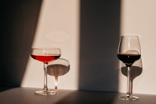 Red wine and vermouth in fragile glasses of various shapes arranged on table near white wall in sunlight