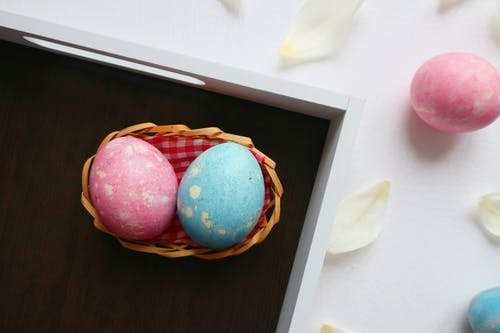 Red and Blue Egg on Brown Woven Basket