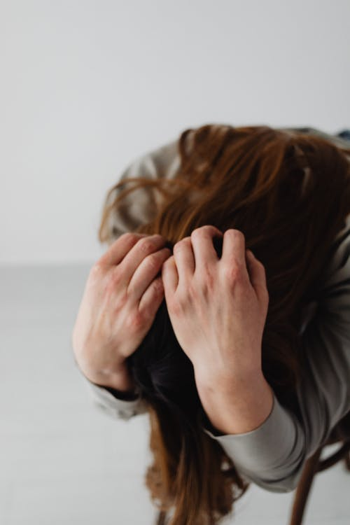 Woman in Gray Long Sleeve Shirt Covering Her Face
