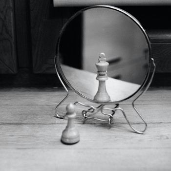 Grayscale Photo of Reversible Mirror in Front of Chess Piece