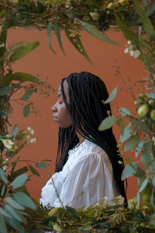 Side view of young serious African American female in white shirt with braids near frame with flowers and plants with green leaves with closed eyes on brown background in studio