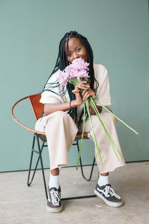 Smiling young African American lady in stylish outfit with cornrows sitting on chair while smelling bouquet of purple flowers while looking at camera in bright room near green wall
