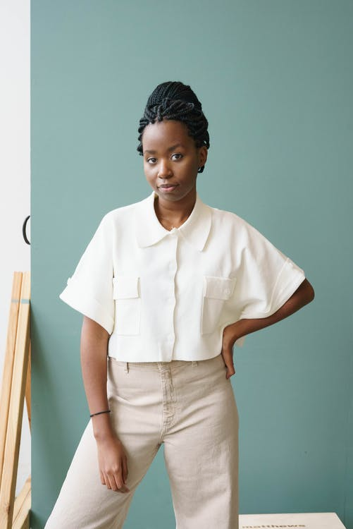 Confident African American woman in trendy apparel with Afro braids in bun looking at camera