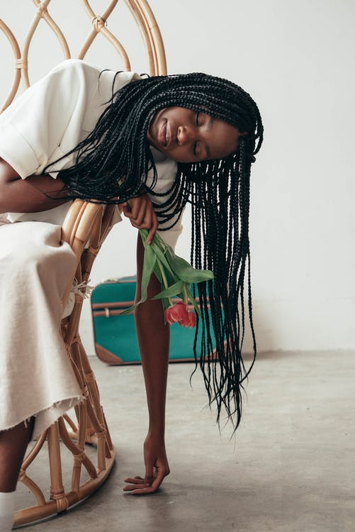 Young ethnic female with Afro braids and blossoming flowers leaning to floor from decorative armchair while representing death concept