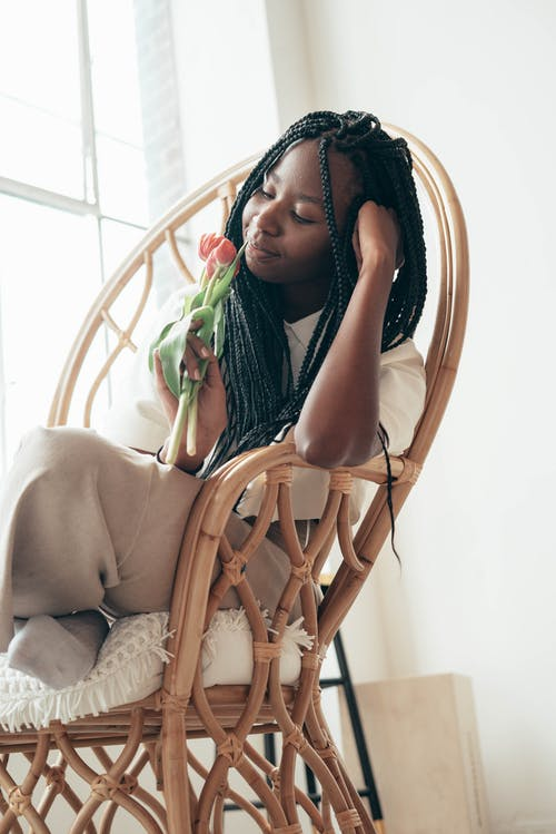 Calm young African American woman smelling fresh flower while resting in armchair