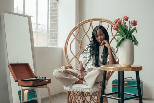 Serious young African American female millennial sitting on bamboo chair with crossed legs near table with vase of fresh tulips and listening to music via vinyl record