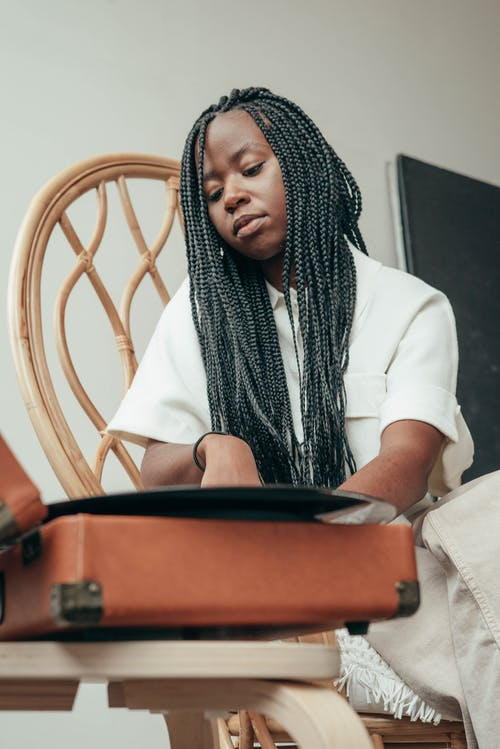 From below of calm young black female meloman with long Afro braids turning on vinyl record player while sitting on chair at home
