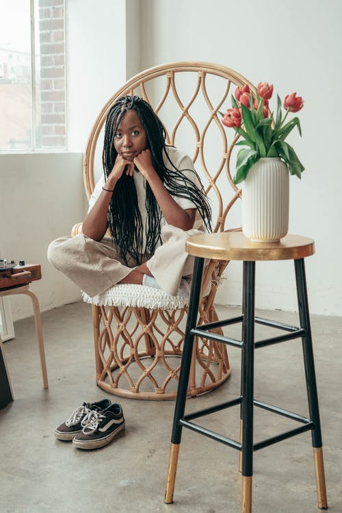 Wistful young black woman leaning on hands while resting on chair in modern apartment