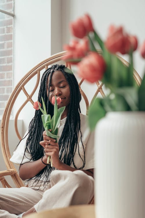Dreamy young African American female millennial with trendy hairstyle enjoying smell of fresh tulips with closed eyes while resting in bamboo armchair at home
