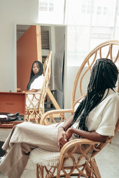 Side view of confident young African American female with long dark braids in casual clothes siting in comfortable bamboo armchair and looking in mirror at home