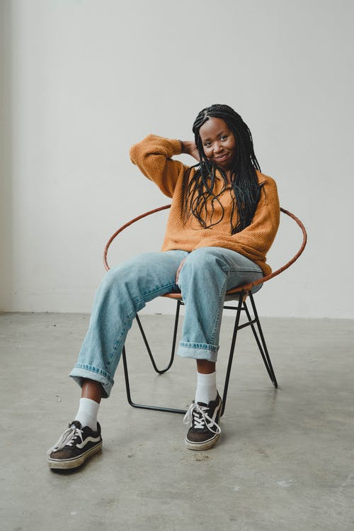 Happy young ethnic female millennial sitting on chair and touching hair