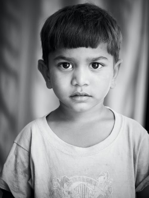 Monochrome Photo of a Cute Boy Looking at Camera