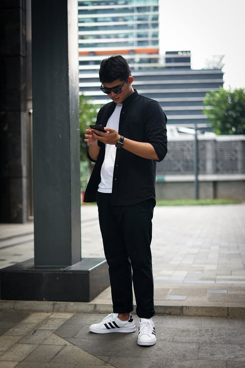 Man in Casual Wear Using His Smartphone