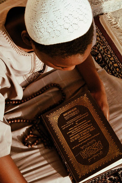 African man in religious with Quran in Muslim mosque