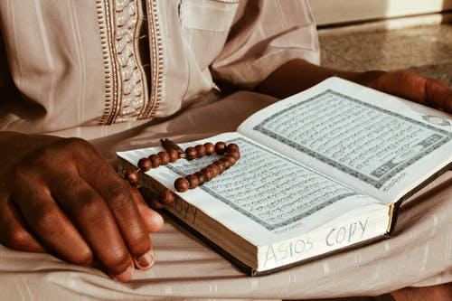 Crop anonymous religious African monk in robe reading holy Islamic book while sitting with rosary beads and praying