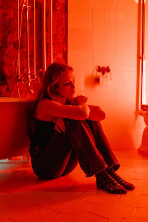 Woman in Black Shirt Sitting on Bathtub