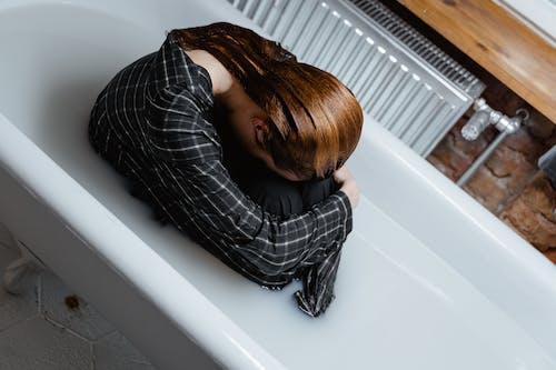 Woman in Black and White Plaid Dress Shirt Lying on Bathtub