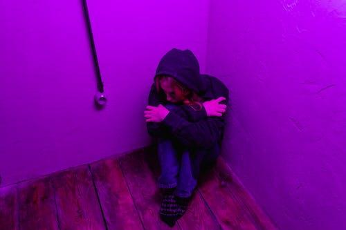 Man in Black Hoodie and Blue Denim Jeans Sitting on Brown Wooden Floor