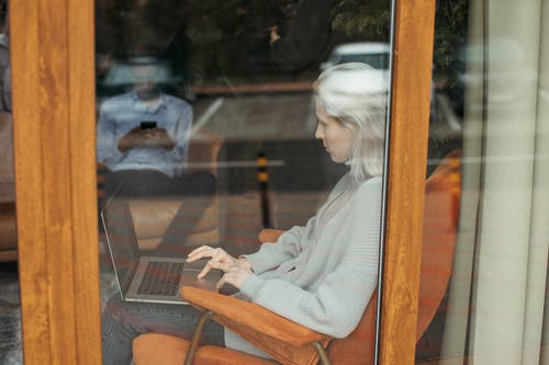 Woman Sitting in Chair and Working on Laptop near Window