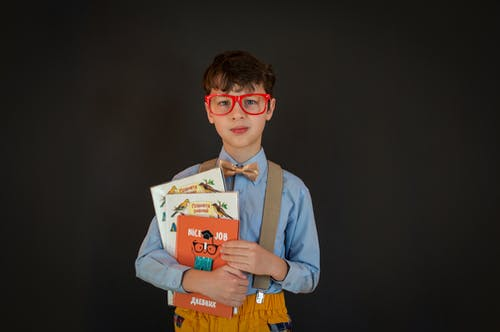 Smart little boy in school uniform with glasses and suspenders holding books while looking at camera and standing against black wall