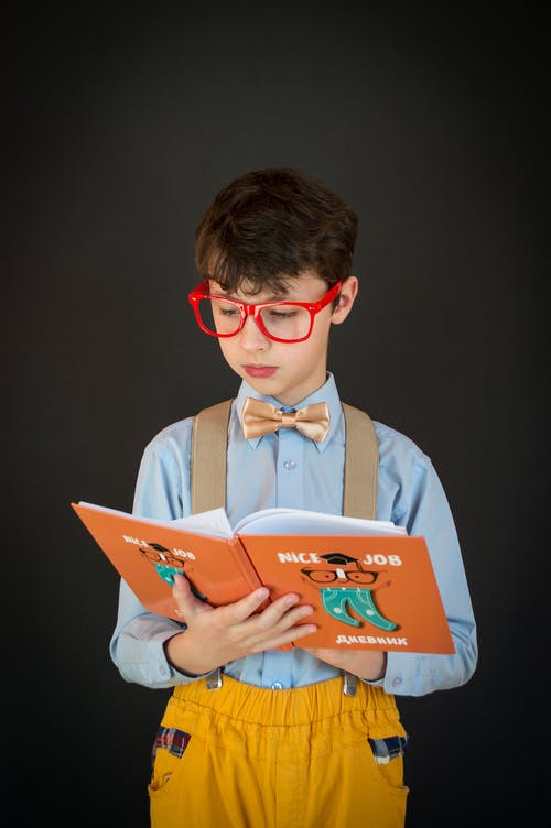 Adorable clever schoolboy in formal wear and red eyeglasses reading book while standing against dark background