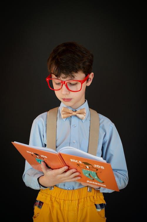 Calm little boy in uniform reading textbook