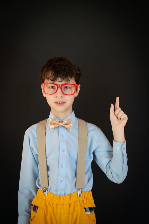 Nerd schoolboy in red eyeglasses blue shirt with bow tie and yellow trousers with suspenders pointing index finger up