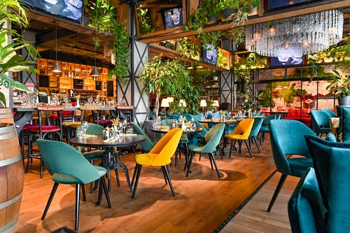 Restaurant Interior with Green and Black Chairs and Tables and Hanging Plants