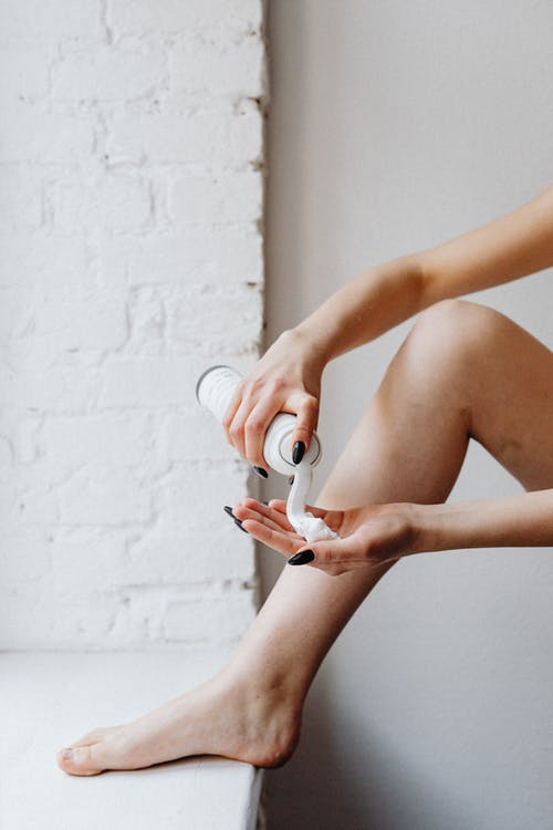 Woman Pouring Shaving Cream on Palm