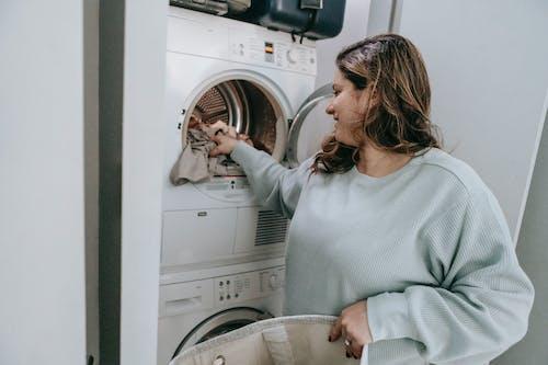 Positive woman loading washing machine