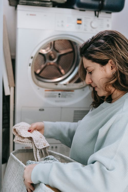 Side view of serious female choosing dirty clothes while sitting in washroom with washing machine during laundry routine at home