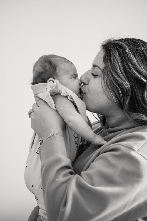 Black and white side view of gentle mother caressing adorable newborn baby while standing in light room on gray background