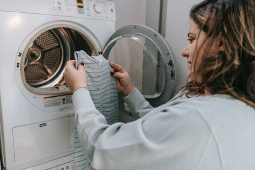 Side view of crop female in casual outfit looking at baby bodysuit before washing clothes in laundry room