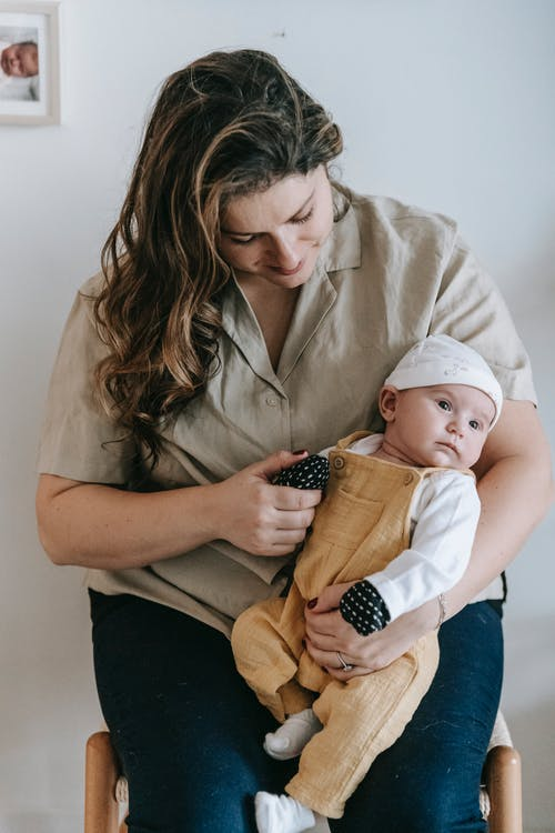 Delighted young mom with long wavy hair in casual outfit sitting on chair and smiling while holding hand of adorable baby at home