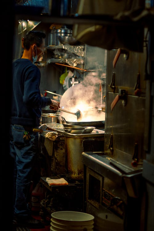 Man in Blue Jacket Cooking