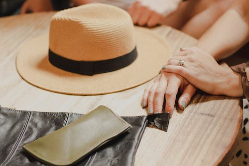 Person Holding Brown Fedora Hat