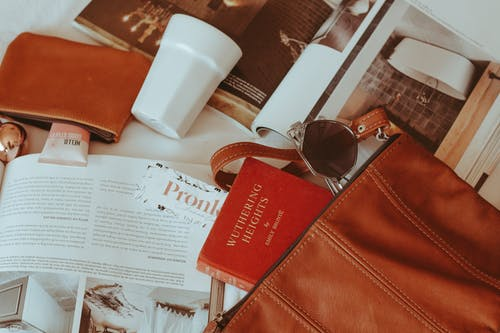 Brown Leather Bifold Wallet Beside White Plastic Cup
