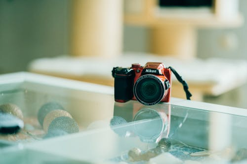 Modern photo camera placed on glass counter