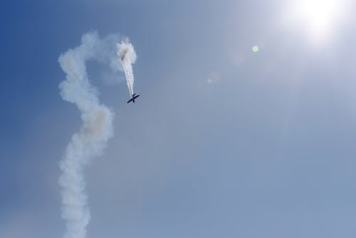 From below of plane flying fast in shiny sky while creating curved trace during show