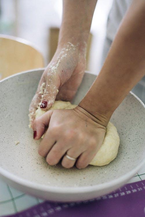 Woman Kneading the Dough in White Ceramic Bowl