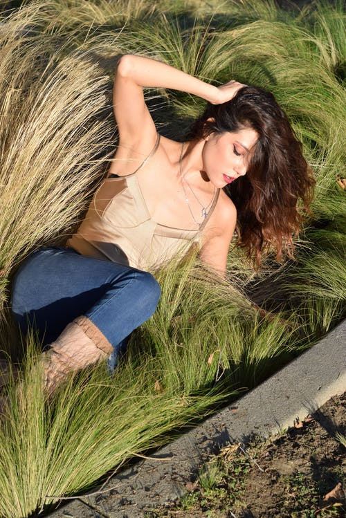From above of young feminine woman in brassiere touching brown hair while lying on lush grass in sunlight