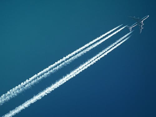 White Airplane With Smoke Under Blue Sky