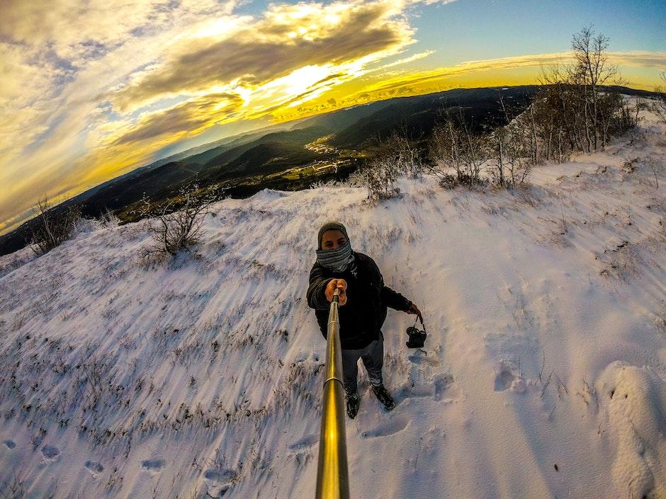 Man Standing on Snowy Terrain